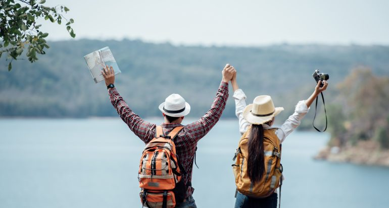 Couple family traveling together,Tourist couple Backpack along mountains and coast, freedom and active lifestyle concept